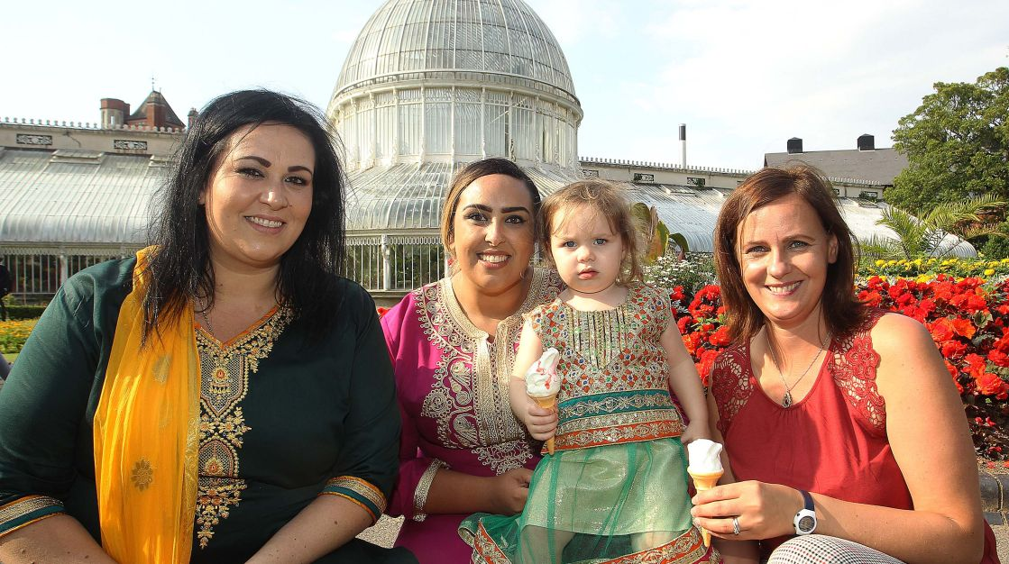 Three women and a child eat ice cream in Belfast's Botanic Gardens.