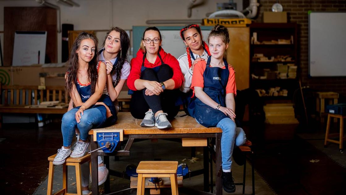 Five young women sit on a workbench in a workshop.