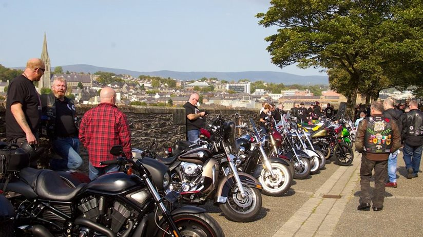 A number of men stand by their motorbikes by an old wall.
