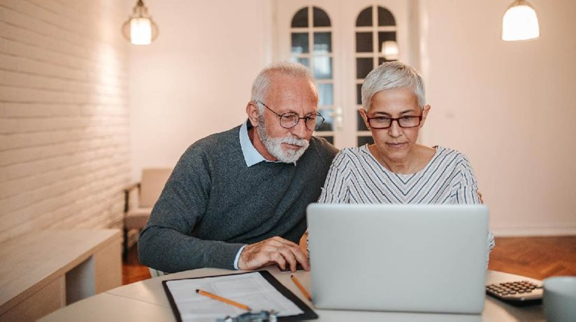 An older man and woman at a laptop computer.