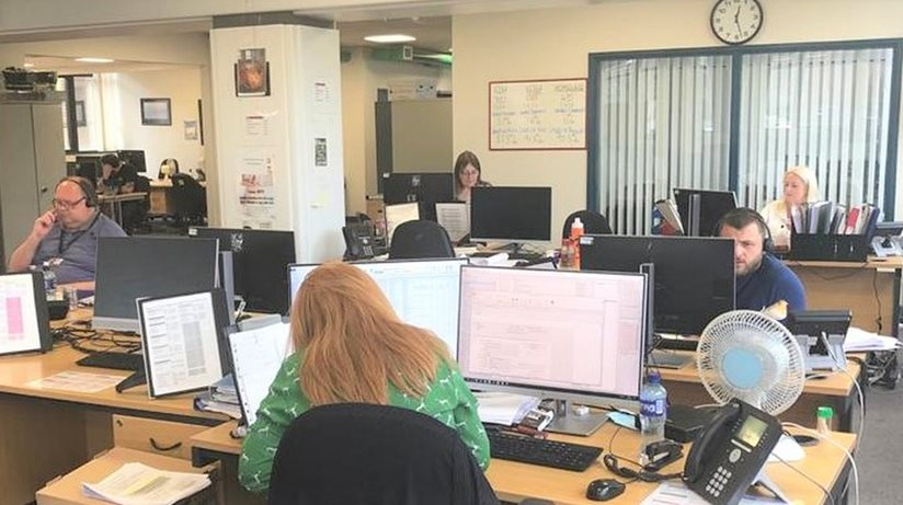 Staff in an office answer calls and work at personal computers.