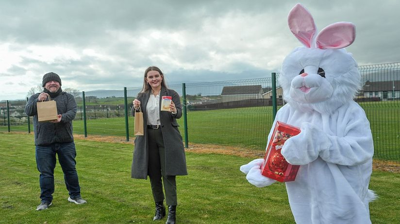 A man and woman hold Easter eggs while posing with the Easter bunny
