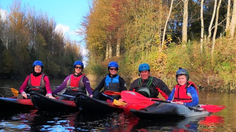 Five canoeists pose on river