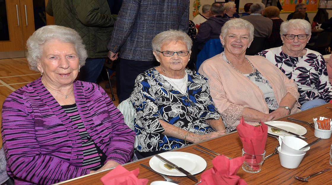 Four older people sit at a table.
