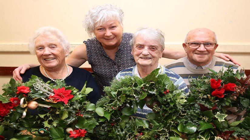 Four older men and women pose with a Christmas wreath.