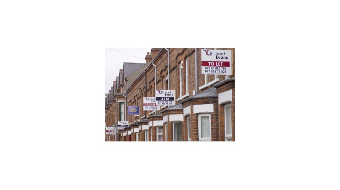 A row of homes with estate agent signs.