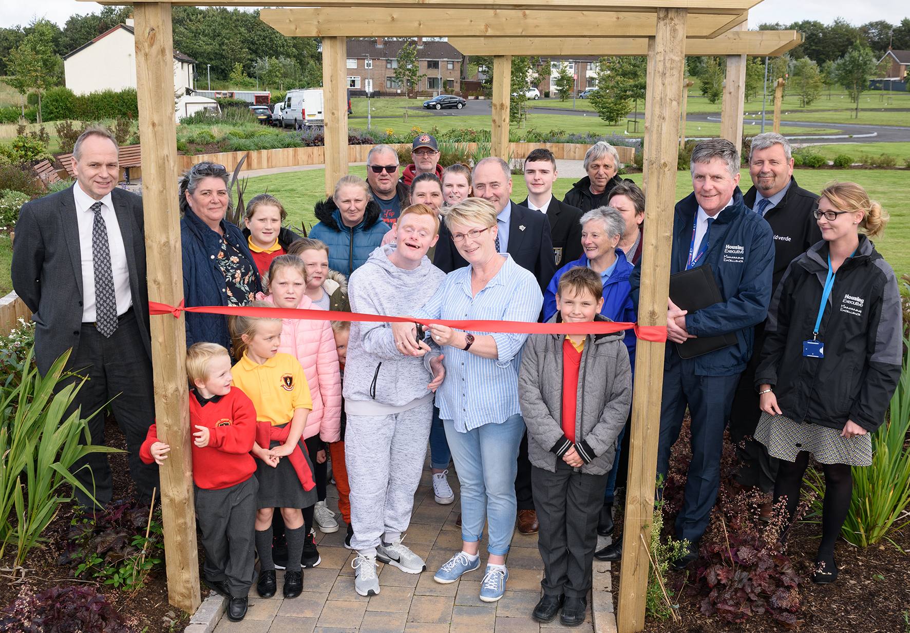 A group of adults and children open a new community garden.