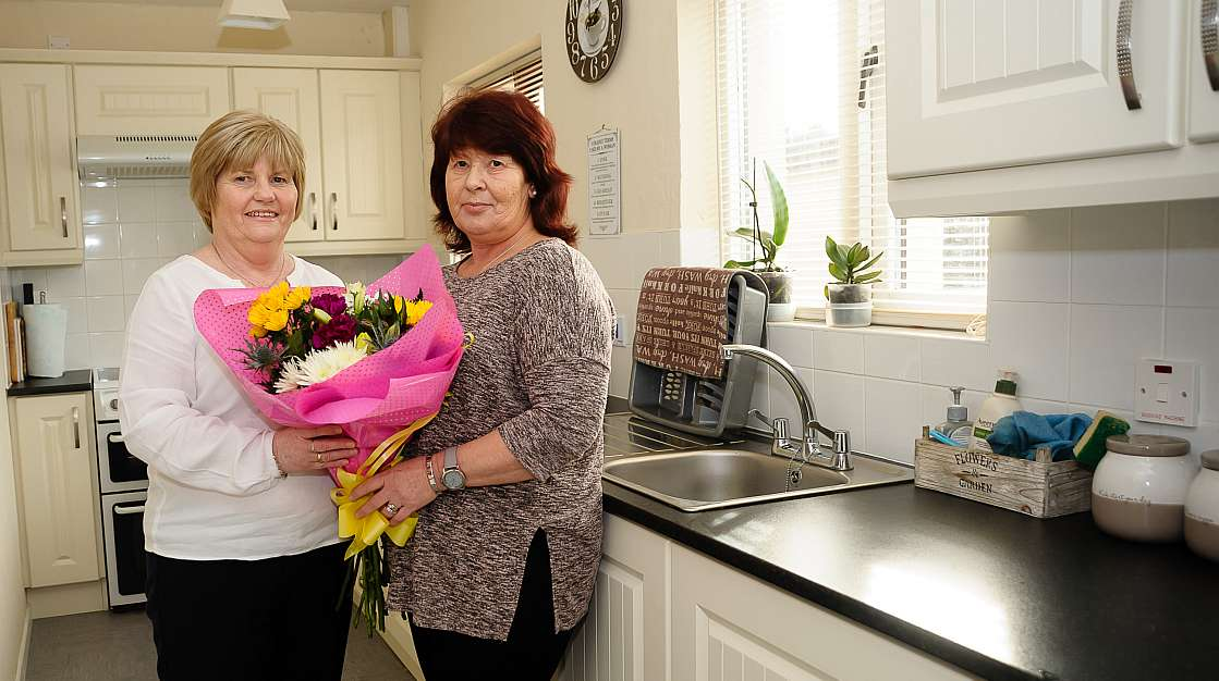 Two women stand in a kitchen with a bunch of flowers