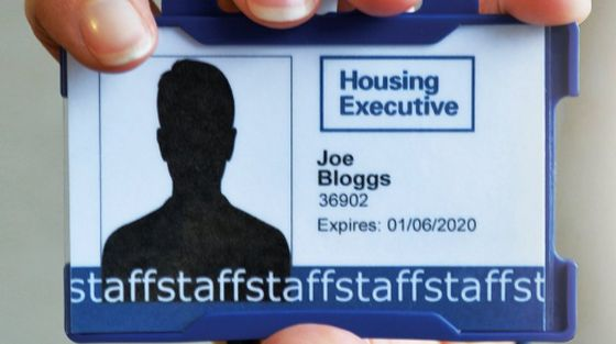 A hand hold a Housing Executive staff pass.